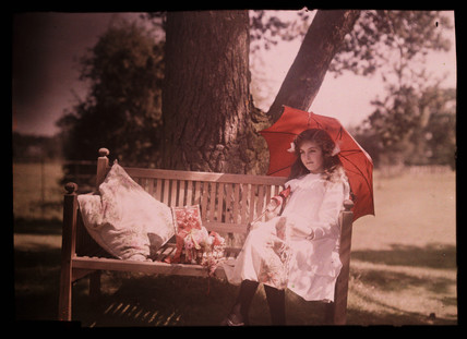 Girl with a parasol sitting on a bench, 1908.