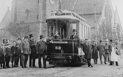 Men and children standing by a tram, c 1900s.