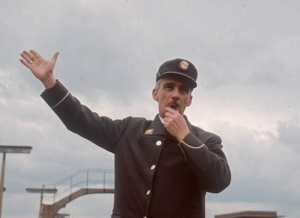 Station guard blowing whistle and signalling to a locomotive, April 1964.