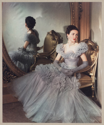 Woman modelling a ball gown in front of a mirror, c 1940s.