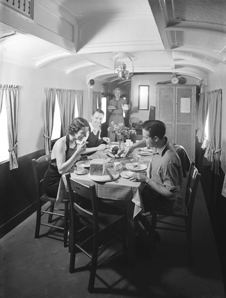 Holidaymakers having a meal in a camping coach, 1936.