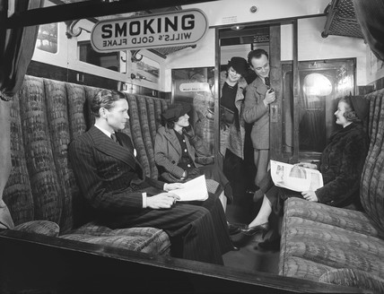 Passengers in a first class railway carriage smoking compartment, 1936.