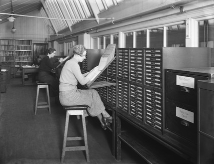 Women office workers using a filing system at a railway station store, 1936.
