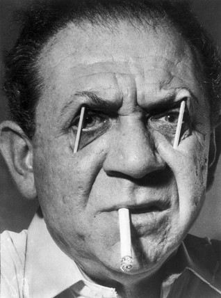 Sid  James with matchsticks in his eyes, whilst smoking a cigarette 1959