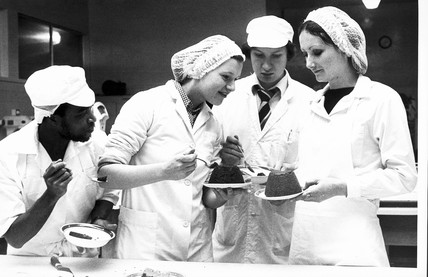 Students eating Christmas pudding, c 1971.