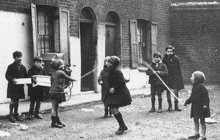 Children playing with a skipping rope in the street, 19 October 1946.