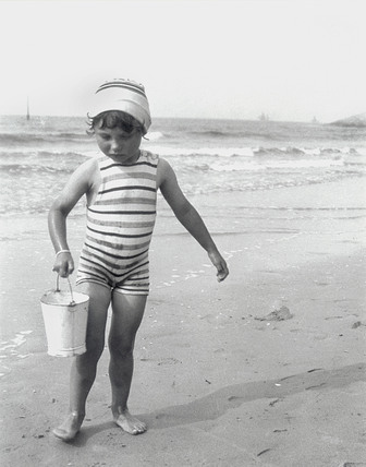 Small girl carrying a bucket on the beach, 1910-1930.