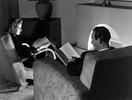 Man and woman reading by a fireside, 1950.