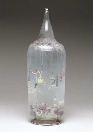 Large glass bottle containing glass amulets, French, c 1870-1920.