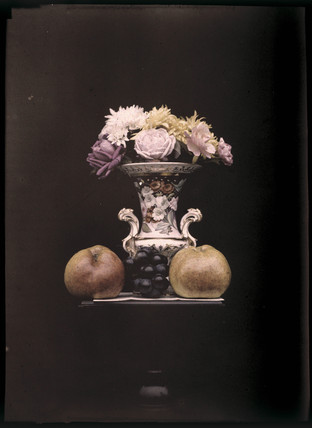 Autochrome of flowers in a vase with fruit, c 1908.