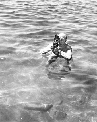 Zoltan Glass taking a photograph standing in the sea, c 1964.