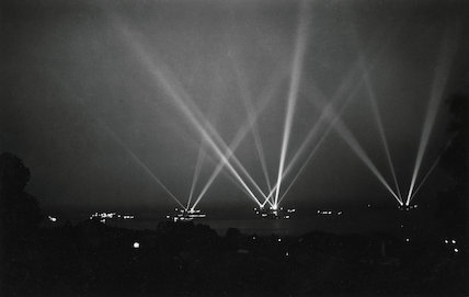 Black and white photograph of searchlight display by warships in Weymouth Bay c. 1930s.
