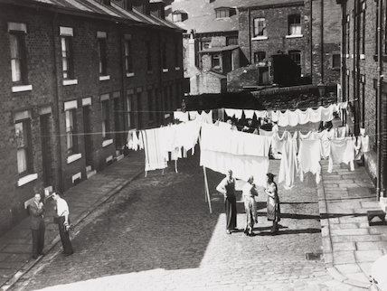 Hanging washing out to dry in the street, c 1930s.
