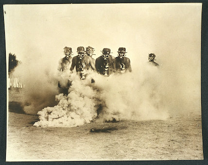 US police recruits in gas masks amidst tear gas clouds