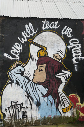 Graffiti of girl embracing an alien with the words Love will tear us apart in East London