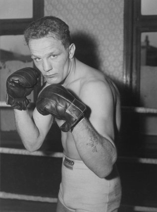 Henry Cooper poses with his boxing gloves on in the boxing ring, 1957