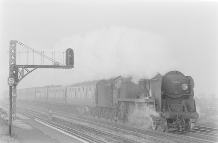 A steam locomotive pulling a passenger train, passing a signal gantry,A1969.70/Box 5/Neg 1258/32