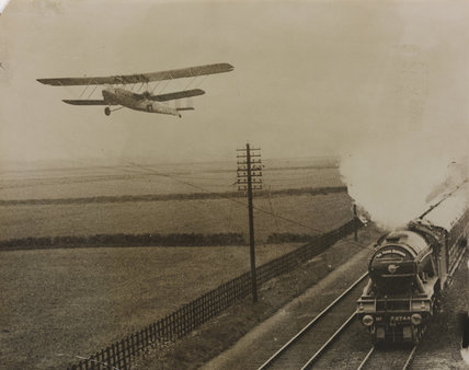 Plane passengers talk to railway passengers while both speed at 90m.p.h. March 1932