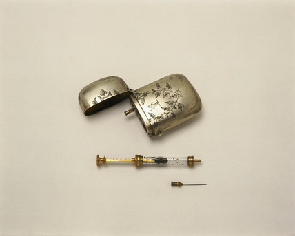 Hypodermic syringe with a spare needle and metal case, late 19th century.