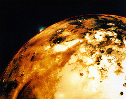 Io, one of the moons of Jupiter, showing a volcanic eruption on the rim, 1979.
