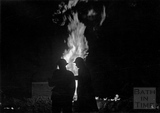 Two wardens, framed in silhouette by a burning gas main, Bath, April 1942
