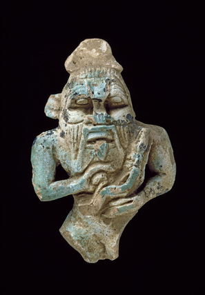 Faience amulet of Bes nursing a Horus