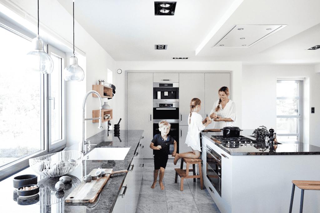 Familie lager frokost på kjøkkenet