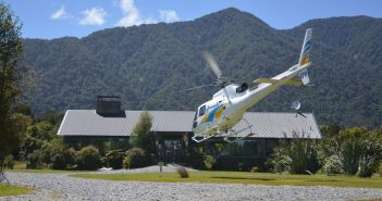 Helicopter lands at the end of the Hollyford Track, Fiordland