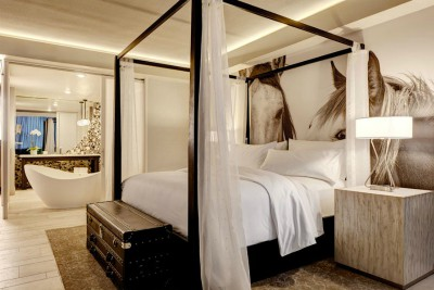 Archer Hotel Austin master bedroom with four poster bed and horse photo
