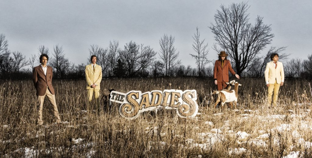 The Sadies standing in a field with goats