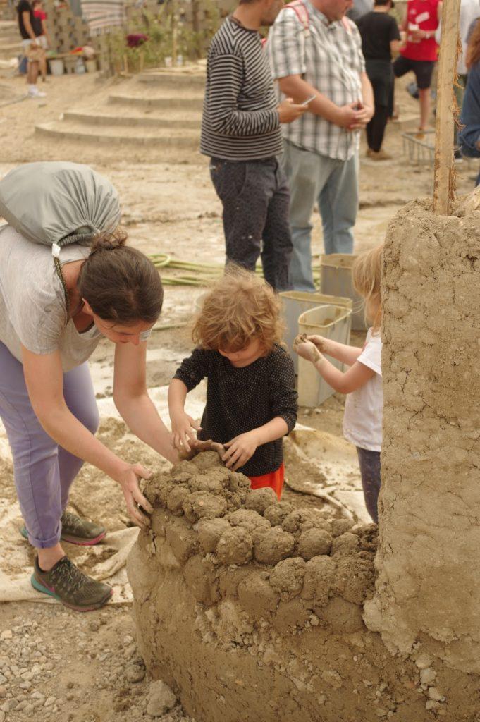 Ue femme et un enfant empilent des boules de terre argileuse afin de réaliser un mur en bauge