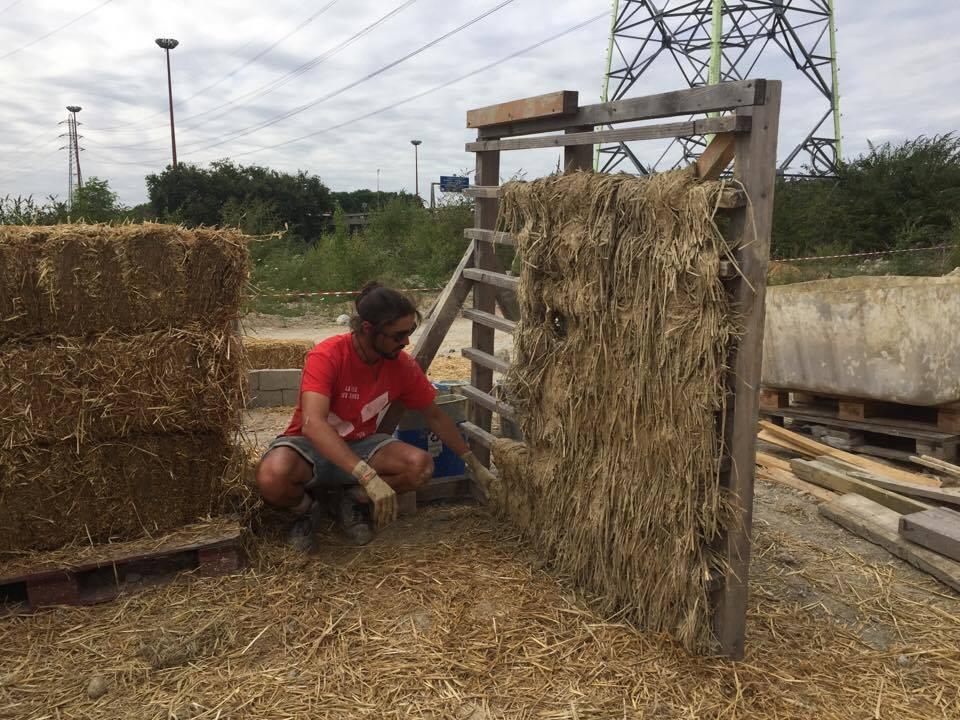 La paille est appliquée sur l'ossature en bois