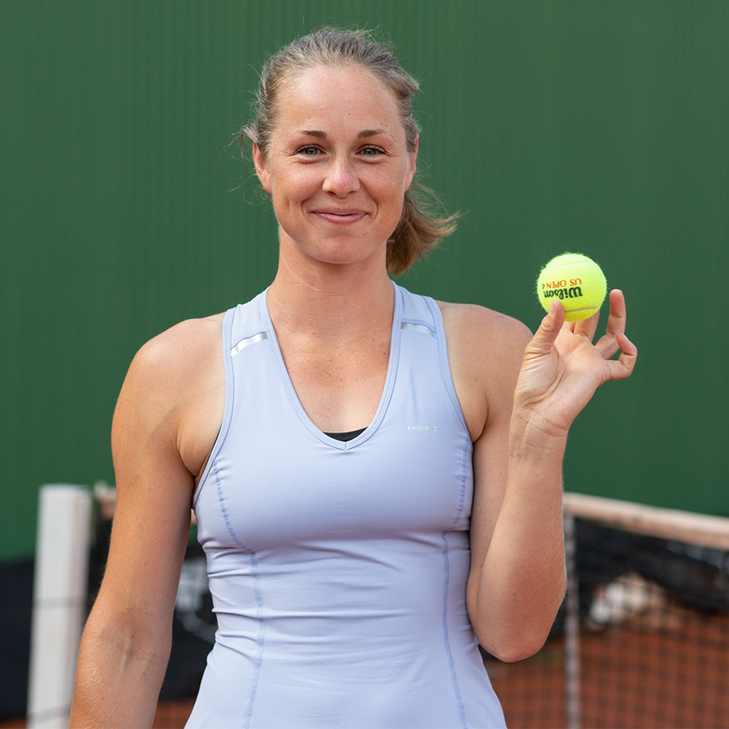 Woman standing on tennis court with tennisball in hand