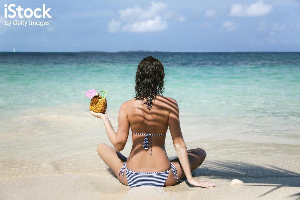 Femme sur une plage avec une boisson