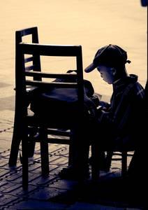Jeune garçon lisant sur une chaise