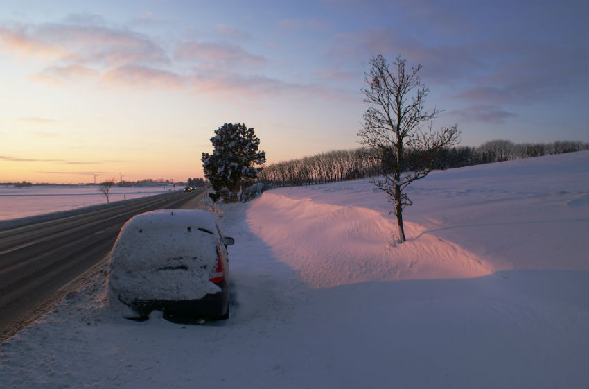 Car at side of road winter sunset