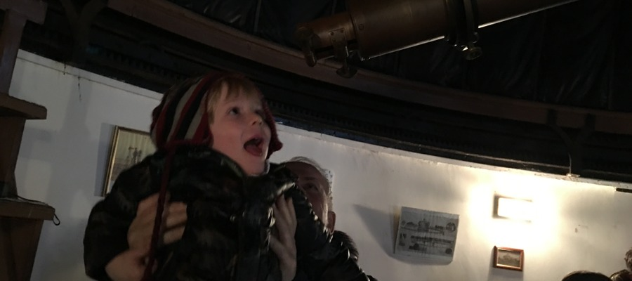 A young boy looking through the telescope at our real-working observatory