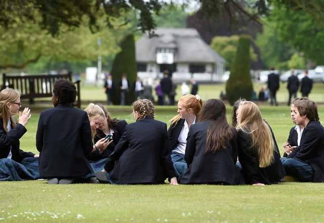 Girls relaxing on the South Front lawns, the cricket pavilion in the background