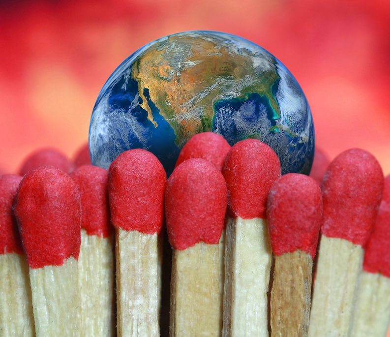 planet earth sitting in some matches depicting global warming