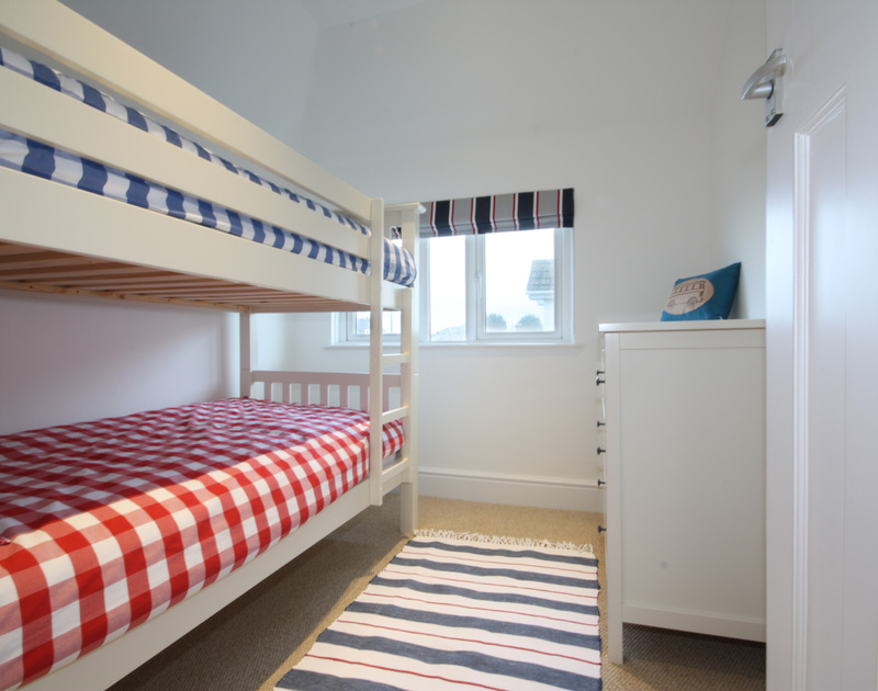 The bunk room of The Moorings, a holiday rental in Rock, Cornwall, with gingham bedspreads and stripy furnishings.