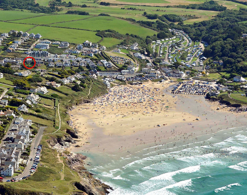 An aerial view of Polzeath beach,sea,village and the location of Westray House, a self catering holiday house in Polzeath, Cornwall.