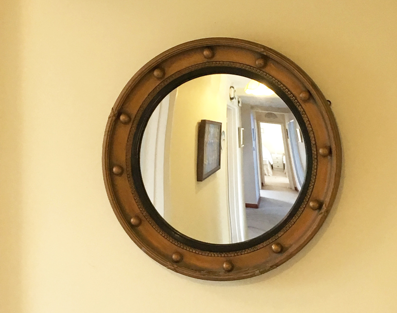 A porthole mirror in Chy An Fos, a self catering holiday house to rent in Rock, Cornwall.