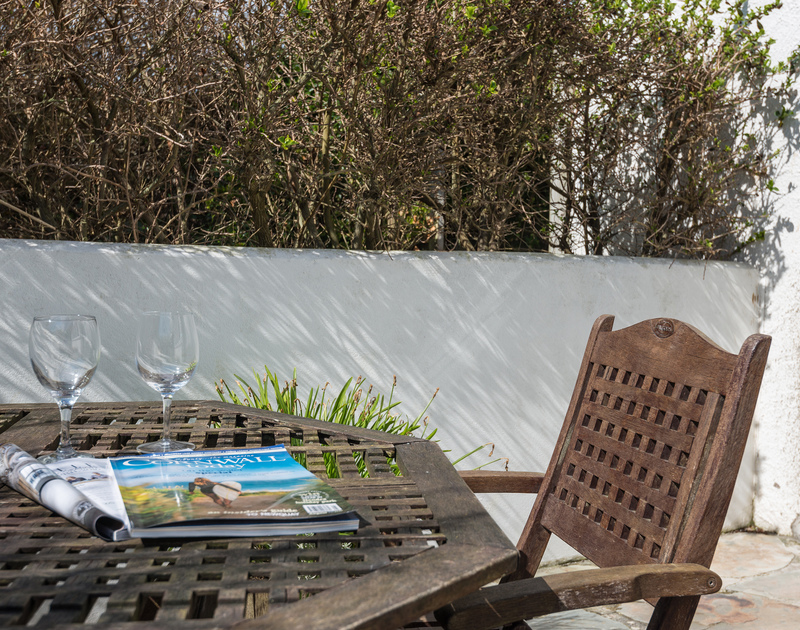 Sheltered private sun terrace with seating and garden access perfect for afternoon drinks at Signal post, a luxurious holiday house to rent in Port Isaac in North Cornwall.