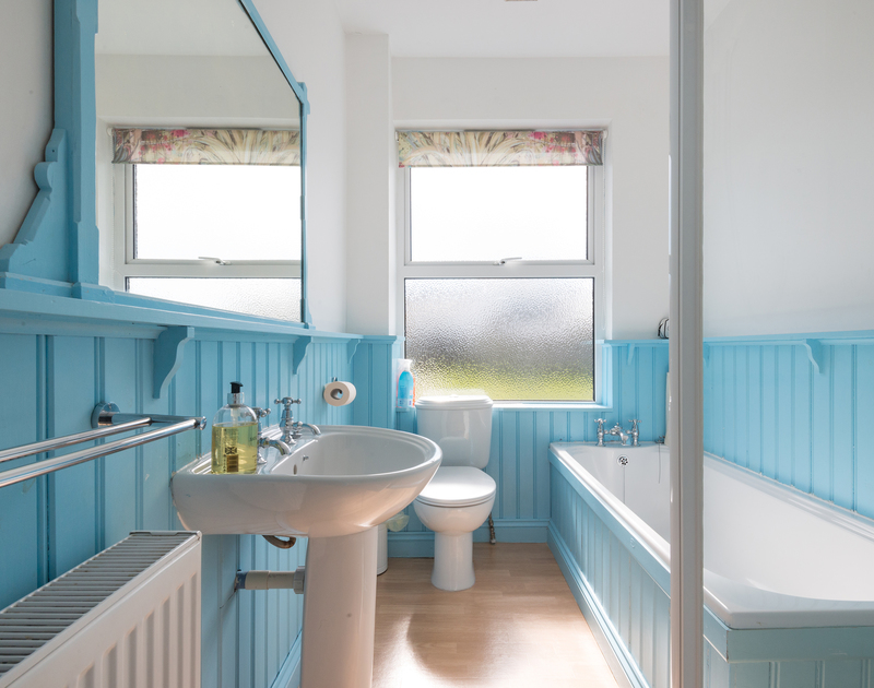 Brightly painted wooden clad bathroom with laminated floor at Signal Post, a self catering holiday rental set between Port Gaverne and Port Isaac in North Cornwall.