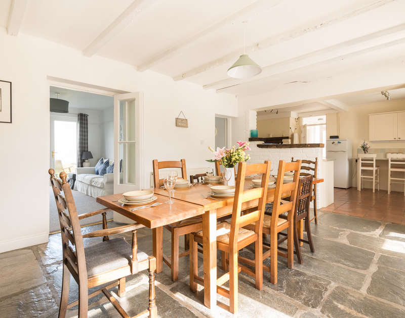 Self catering holiday house Signal Post in Port Isaac, North Cornwall has a sunny dining room with slate floors, large dining table and open plan kitchen area.