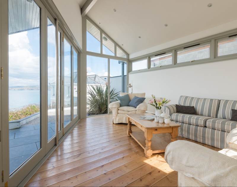 Comfortable and bright sun lounge with large glass sliding doors and windows and spectacular sea views out across the bay at Signal Post, a self catering holiday house at Port Isaac in Cornwall.