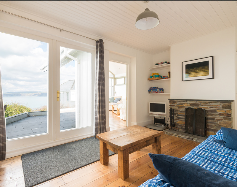 Small light-filled sitting room with french doors to sun deck with sea views at Signal Post, a luxury self catering holiday house in Port Isaac, North Cornwall.