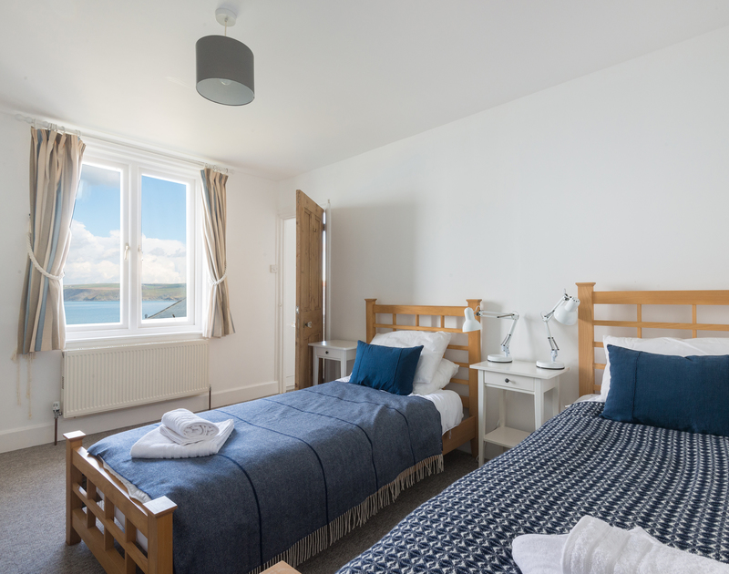 The twin bedroom with lovely sea and rugged coastal views at Signal Post, a luxury self catering holiday house in a fantastic position between Port Gaverne and Port Isaac in North Cornwall.