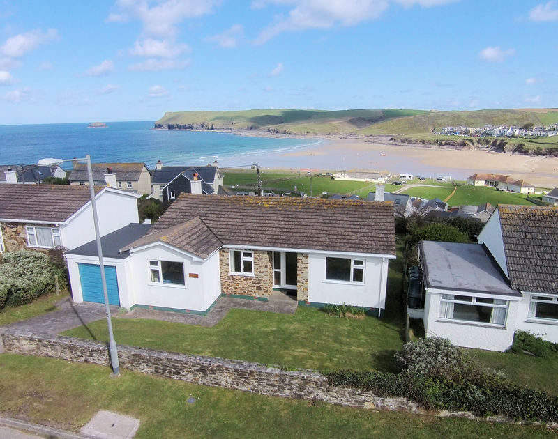 An aerial view of the exterior of Zapadiah, a self-catering holiday let, with Polzeath beach in the background.
