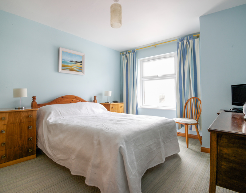 Spacious double bedroom of Slipway 16, holiday house in Rock, Cornwall with king size bed, tv and storage space.
